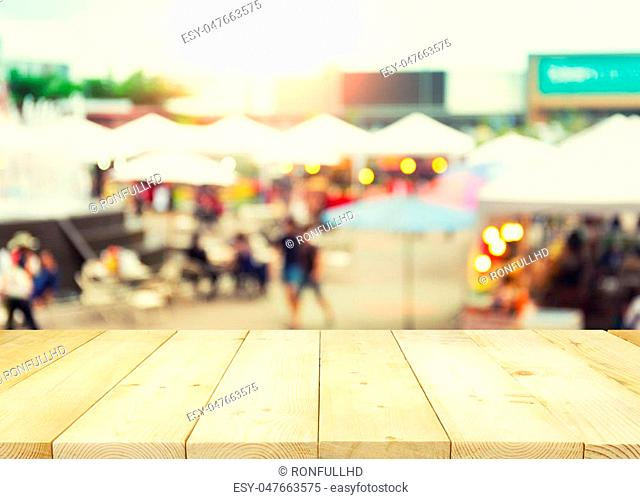 Blurred photo of food exhibition fair montage with wood table top for background