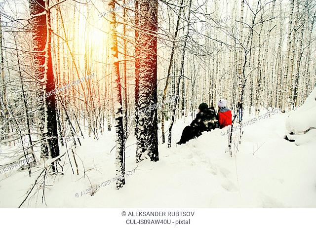 Couple sitting in snowy forest, watching sunset, Russia