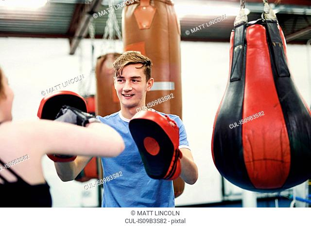 Female boxer training, punching teammate's punch mitt