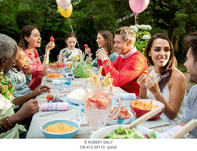 Family and friends enjoying birthday garden party at patio table