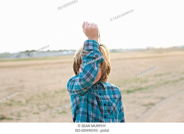 Boy with arm in front of face