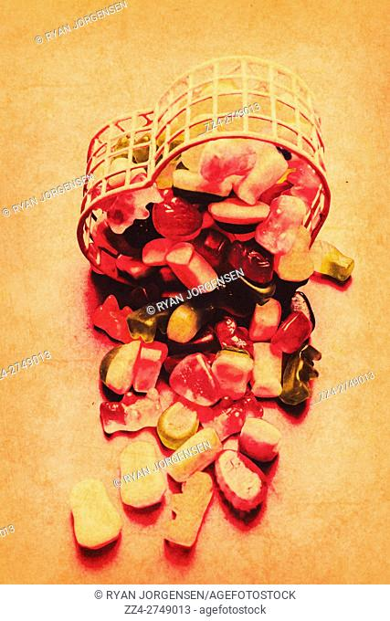 Vintage concept photo on a tipped out lolly container pouring out its heart on a antique surface. Sweetheart art