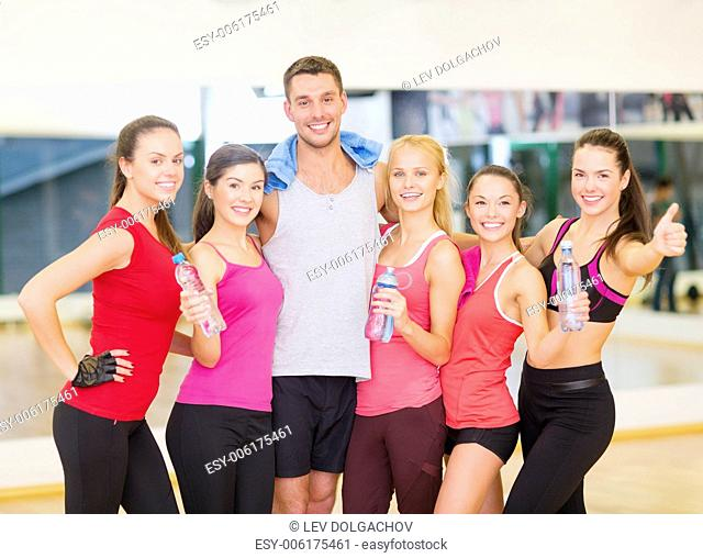 fitness, sport, training, gym and lifestyle concept - group of happy people in the gym with water bottles and towel showing thumbs up