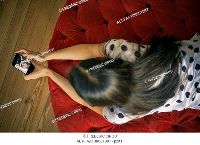 Woman relaxing on ottoman, taking selfie with smartphone