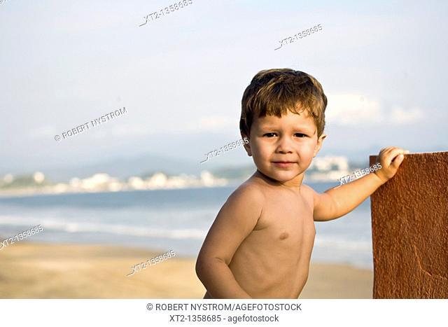 A young toddler stands against a wall beside the ocean and beach in Mexico
