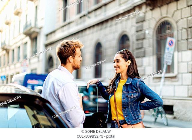 Couple talking in street, Milan, Italy