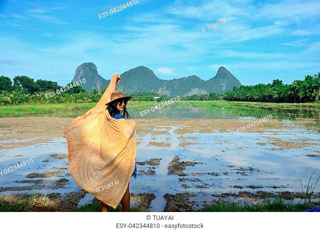 Thai women with shawl fabric natural color portrait at outdoor near Khao Oktalu Mountain or The Hole Mountain with rice field at Phatthalung province of...