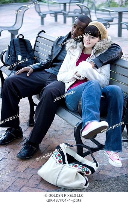 Contemplative young inter-racial couple embracing on a park bench