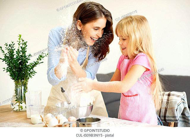Mother and daughter baking together, fooling around