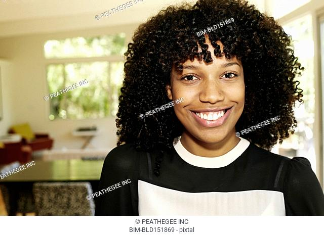 Mixed race businesswoman smiling in dining room