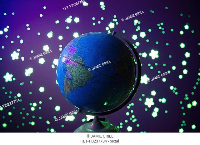 Fluorescent stars and globe on blue background, studio shot
