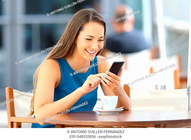 Happy woman using a smart phone alone sitting in a bar terrace