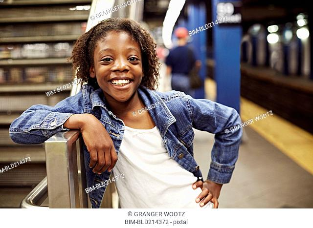 Smiling girl leaning on subway staircase