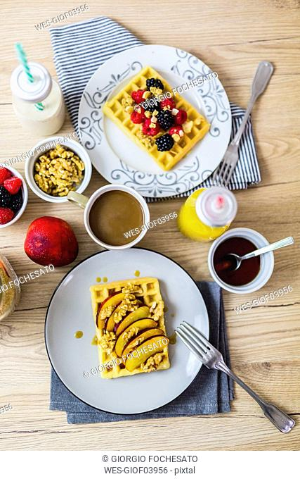 Various garnished waffles on breakfast table