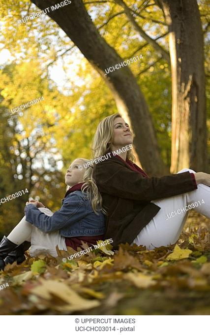 Mother and daughter sitting in autumn leaves