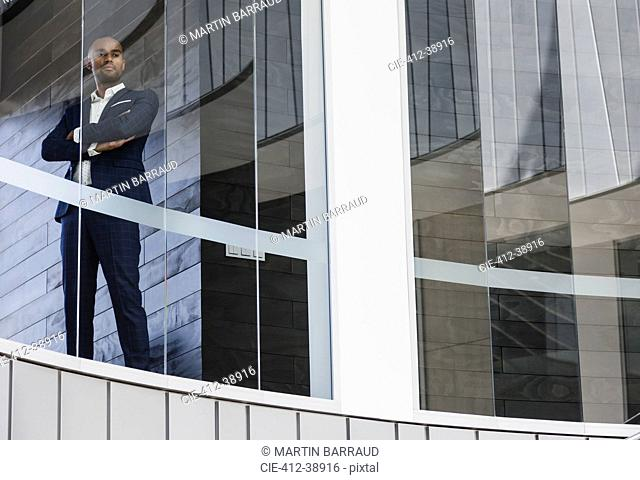 Portrait confident CEO businessman standing in office window