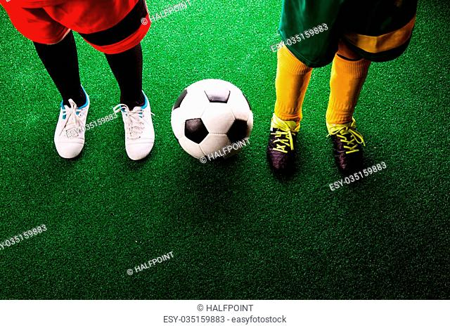 Legs of two unrecognizable little football players with soccer ball against artificial grass. Studio shot on green background