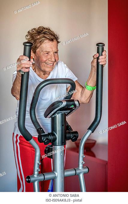 A very senior woman using an exercise machine