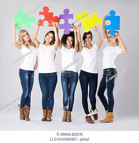 Multi-ethnic girls with colored jigsaw puzzle. Debica, Poland