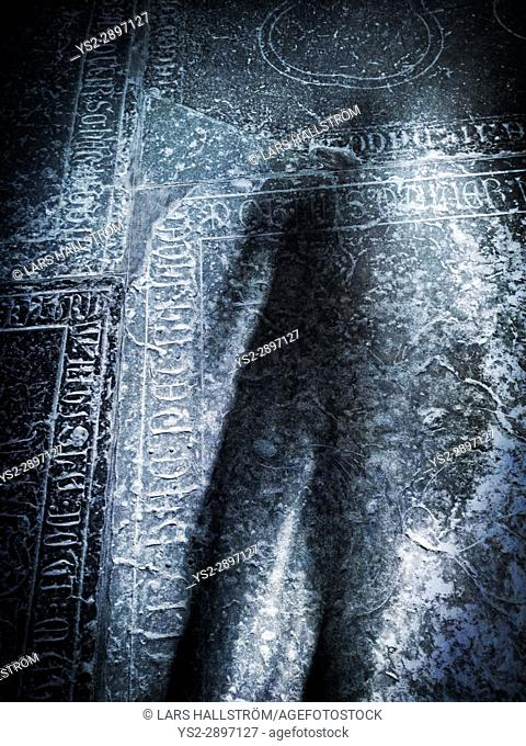Scary shadow on old grave stone in church. Concept of death, crime and horror