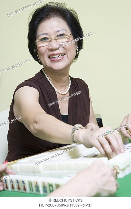 Portrait of a senior woman playing mahjong