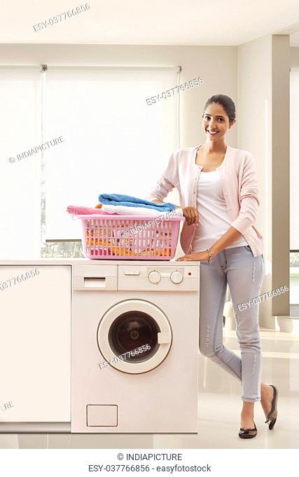 Portrait of woman standing near washing machine with laundry basket
