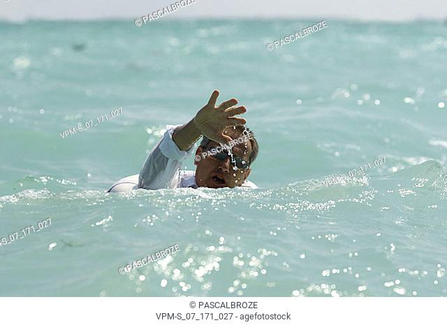 Mature man in water with a life belt