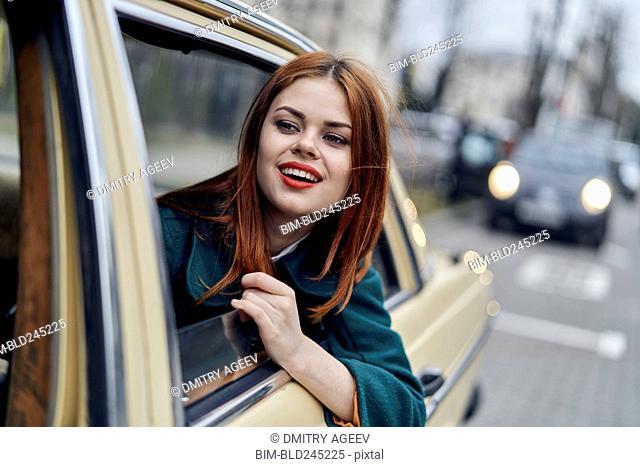 Smiling Caucasian woman in back seat of car