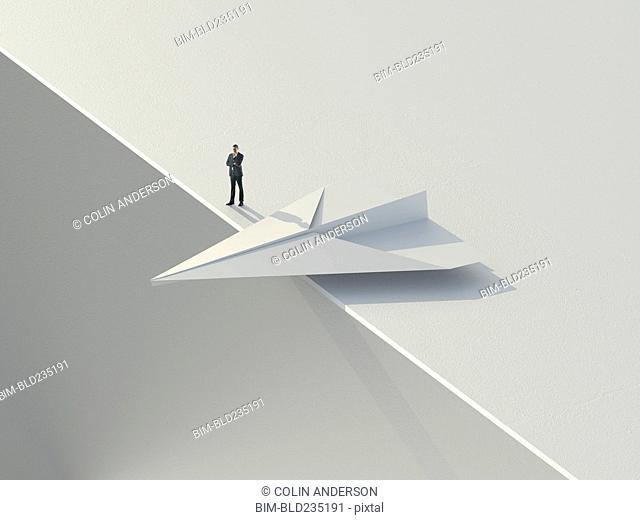 Caucasian businessman standing near paper airplane teetering on an edge