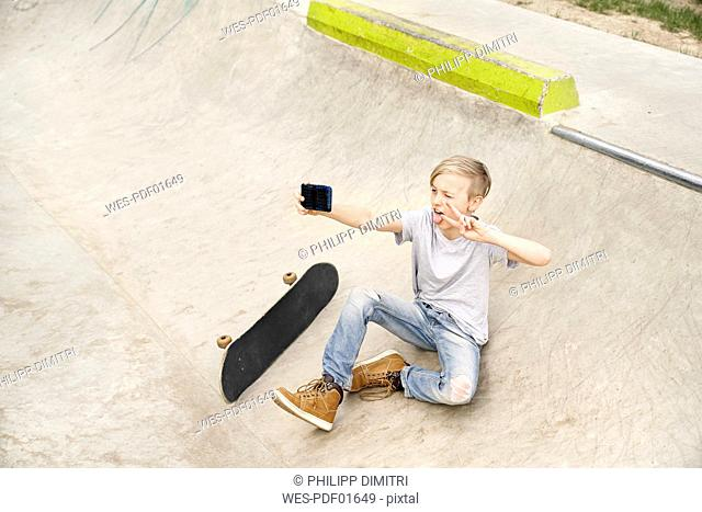 Boy with skateboard taking selfies with smartphone