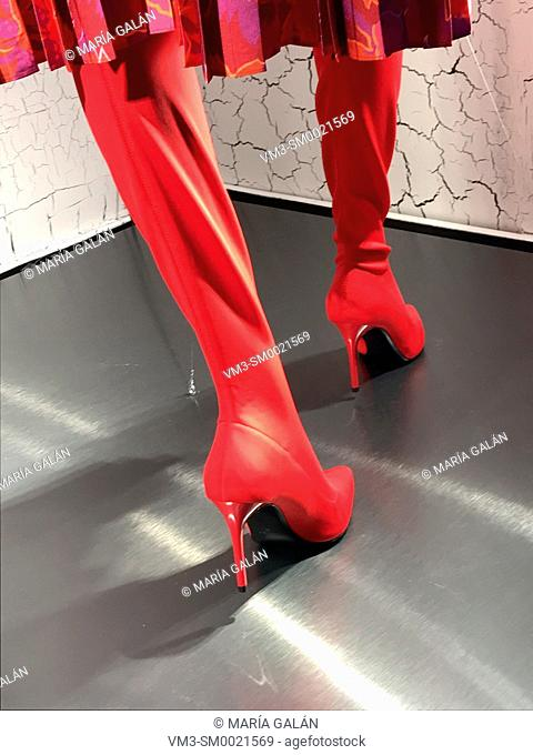 Mannequin's feet wearing red high-heeled boots in a shop window. Serrano street, Madrid, Spain