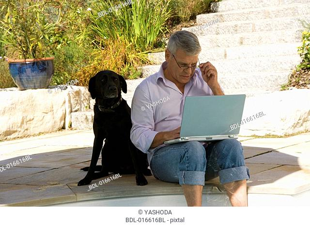 mature man sitting at swimming pool with dog and working with laptop computer