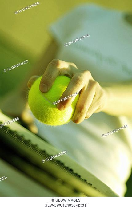 Mid section view of a woman holding a tennis ball and a tennis racket