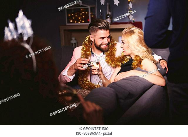Man and woman at party, sitting on sofa, holding drinks, making a toast