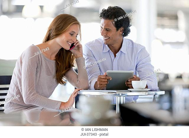 Couple using cell phone and digital tablet at cafe table