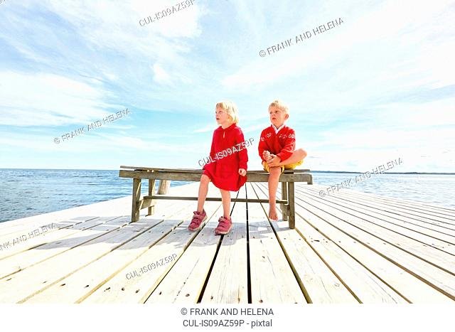 Two young friends sitting on bench on wooden pier