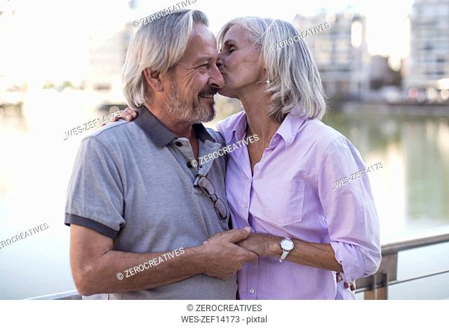 Senior couple taking a city break, kissing and embracing