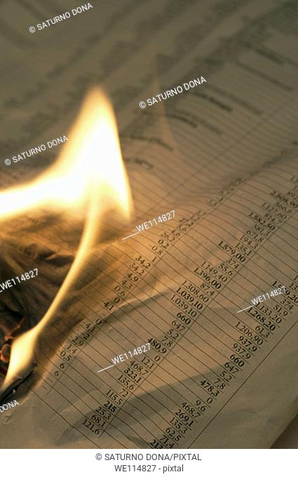 Burning financial newspaper with stock index
