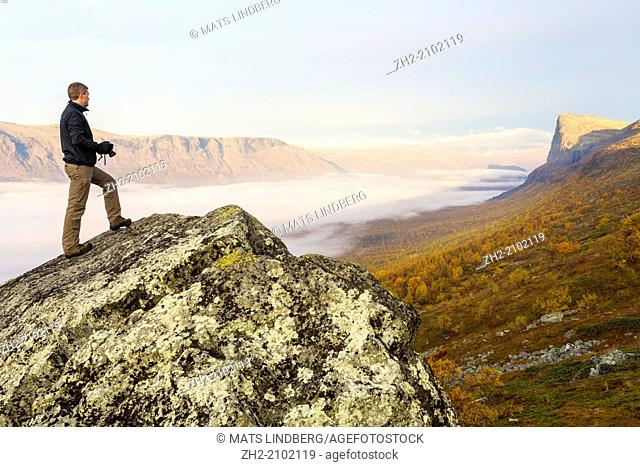Man, 35-40 years old, watching view over Sarek national park standing on a rock in beautiful morning light with fog laying over the valley in sweden
