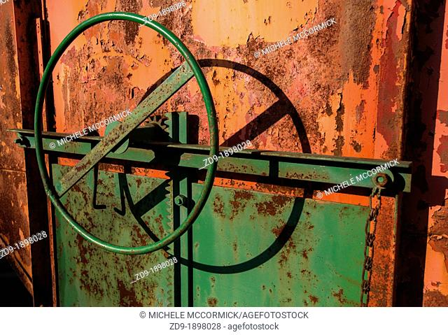A rust-covered piece of farm equipment is brightly colorful in the morning sun