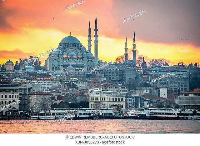 The sun sets over Suleymaniye Mosque and the city of Istanbul, Turkey creating a warm glow on the waters of the Golden Horn