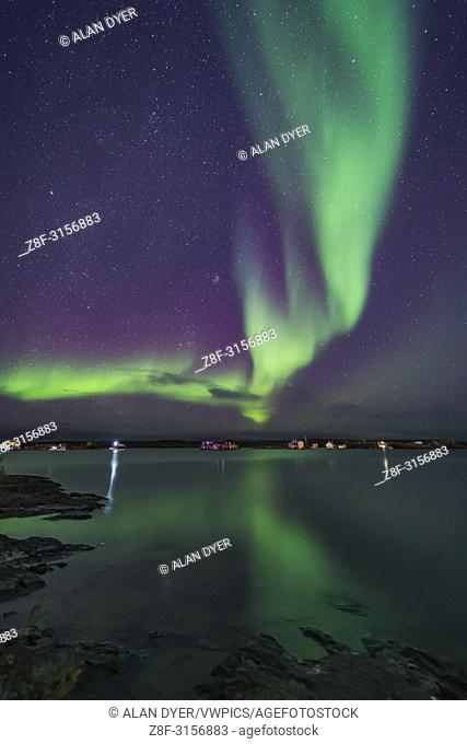A curtain of aurora sweeps over the houseboats moored on Yellowknife Bay in Yellowknife, NWT, on September 11, 2018. . . The Pleiades and Hyades star clusters...