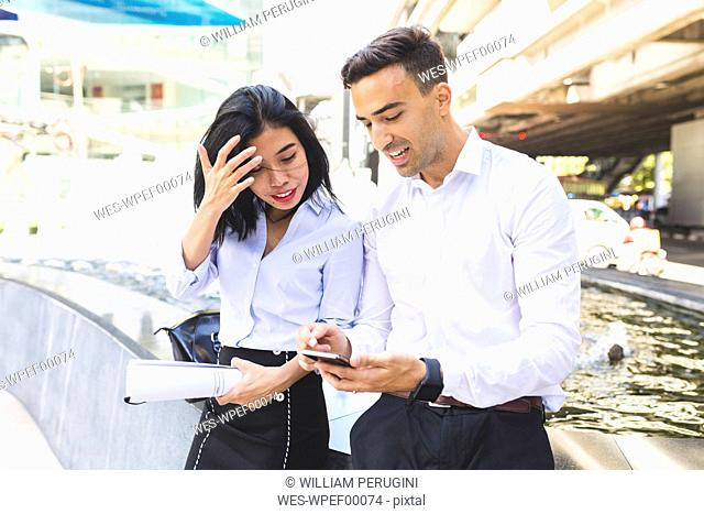 Thailand, Bangkok, businessman and businesswoman in the city with cell phone