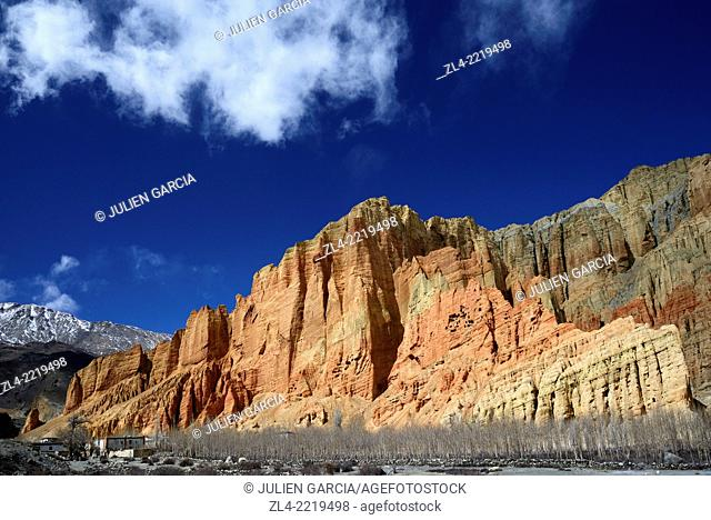 The village of Dhakmar and red cliff with caves. Nepal, Gandaki, Upper Mustang (near the border with Tibet)