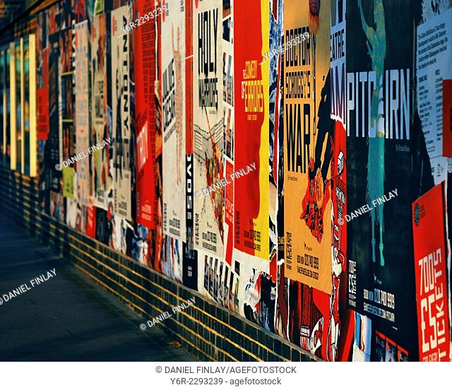 Playbills on the wall in front of the Globe Theatre on the banks of the River Thames in Southwark, London, England, in late evening light