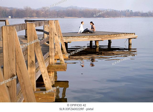 Couple talking on jetty overlooking lake