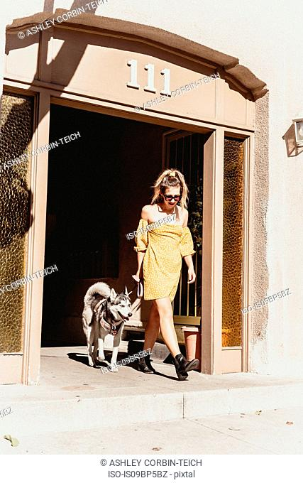 Young woman with pet dog at entrance of building