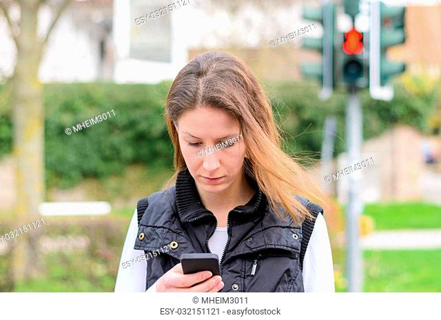 Young woman checking for text messages on her mobile phone as she walks across the street at a red pedestrian crossing