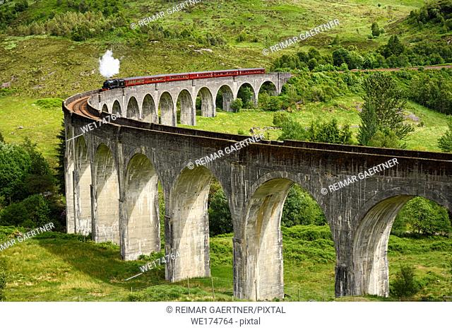 Red heritage Jacobite coal fired Steam Train used in Harry Potter films at Glenfinnan viaduct in the Scottish Highlands Scotland UK