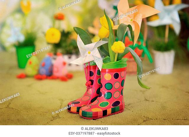on a green background with flowers rubber boots and paper toys